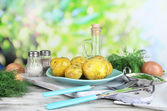 Boiled potatoes on platen on wooden board near napkin on wooden table on nature background — Stock Photo