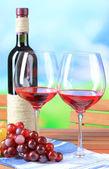 бокалов вина на салфетке на деревянный стол на фоне природы — Стоковое фото