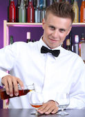 Bartender is pouring cognac into glass — Stock Photo