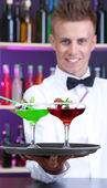 Portrait of handsome barman with different cocktails cocktail, at bar — Stock Photo