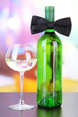 Black bow tie on wine bottle on bright background — Stock Photo