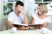Beautiful young romantic couple with photo, at home — Foto de Stock