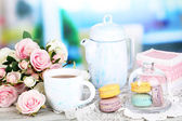 Macaroons in bowl on wooden table on room background — Stock Photo
