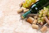 Bottiglia di vino, uva e tappi su vecchio di carta — Foto Stock