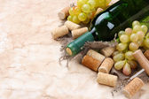 Bottle of wine, grapes and corks on old paper background — Stock Photo