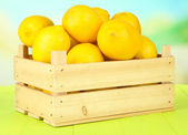 Ripe lemons in wooden box on table on bright background — Stock Photo