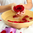 Стоковое фото: Womhands with wooden bowl of water with petals, on blue background
