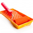 Roller in tray with orange paint isolated on white — Stok fotoğraf