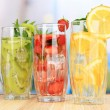Glasses of fruit drinks with ice cubes on table in cafe — Stock Photo #29303037