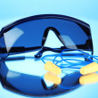 Foto Stock: Eyeglasses tools and earplugs on blue background