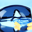 Stock Photo: Eyeglasses tools and earplugs on blue background