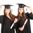 Stock Photo: Two happy graduating students isolated on white