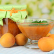 Apricot jam in glass jar and fresh apricots, on wooden table, on bright background — Stock Photo