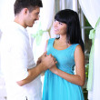 Beautiful young romantic couple near window — Stock Photo