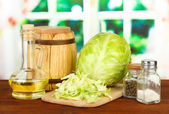Green cabbage, oil, spices on cutting board, on bright background — Foto Stock