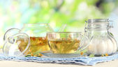 Kettle and cup of tea with linden on napkin on wooden table on nature background — Stock Photo