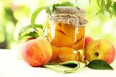 Glas Dosenpfirsiche und frische Pfirsiche auf Holztisch, außerhalb — Stockfoto