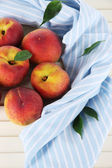 Peaches on napkin on wooden table — Stock Photo