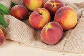 Peaches on sackcloth on wooden table — Stock Photo