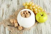 Unrefined sugar in white sugar bowl on wooden background — Stock Photo