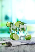 Glasses of cocktail with ice on board on napkin on wooden table on room background — Stock Photo