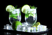 Glasses of cocktail with ice on metal tray on black background — Stock Photo