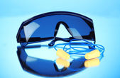 Eyeglasses tools and earplugs on blue background — Стоковое фото