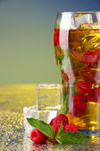 Iced tea with raspberries and mint on blue background — Stock Photo