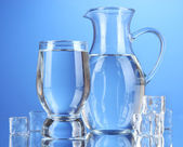 Glass pitcher of water and glass on blue background — Stock Photo