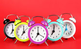 Colorful alarm clock on red background — Stock Photo