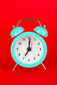 Blue alarm clock on red background — Stock Photo