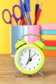Green alarm clock on table on yellow background — Stock Photo