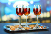 Glasses of amaretto liquor and roasted almonds, on tray, on bright background — Stock Photo