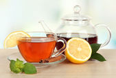 Cup of tea with lemon on table on light background — Stock Photo