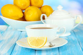 Cup of tea with lemon on table on blue background — Stock Photo
