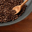 Stock Photo: Black wok pwith coffee beans on wooden table, close up