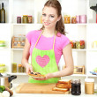 Young woman cooking in kitchen — Stock Photo #29311771