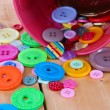 Stock Photo: Colorful buttons strewn from bucket close-up