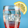 Stock Photo: Glass of water and ice on blue background