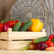 Fresh vegetables in wooden box on burlap and wicker background — Stock Photo #29312389