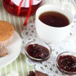 Yummy jam in bank on napkin on wooden table — Stock Photo