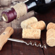 Corkscrew with wine corks and bottle of wine on wooden table close-up — Stock Photo #29313855