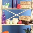 Beautiful white shelves with different home related objects, on color wall background — Stock Photo