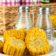 Flavored boiled corn on  plate on wooden table on natural background — Photo