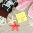 Composition with flip flops, binoculars, notepad and money, on sand background — Foto de Stock