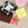Composition with flip flops, binoculars, notepad and money, on sand background — Stock Photo