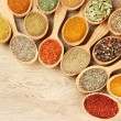 Assortment of spices in wooden spoons on wooden background — Stock Photo #29315931