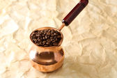 Coffee pot with coffee beans on beige background — Stock Photo
