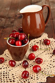 Ripe red cherry berries in cup on wooden table close-up — Stockfoto