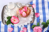 Cup of tea from tea rose on metallic tray on tablecloth — Stock Photo